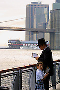 A Jewish man prays with his daughter not far from the smoking remnants of Lower Manhattan just days after the 9/11 attacks as Jews gathered along the river.