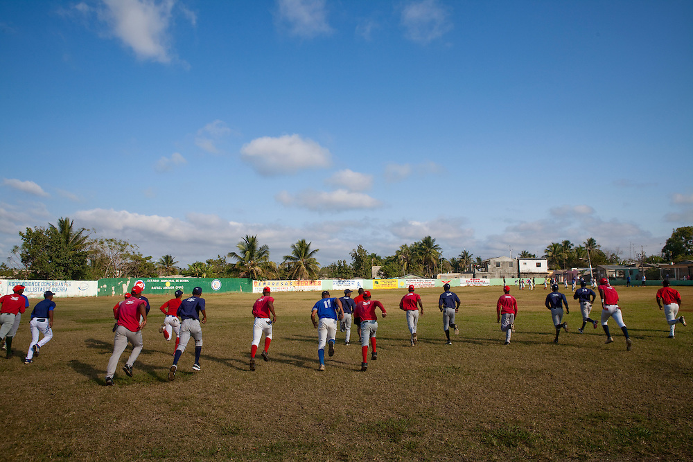 The Warriors baseball team jogs onto the field to warm up before a showcase for Major League Baseball scouts on Friday, February 26, 2010 in San Antonio de Guerra, Dominican Republic.