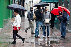 © licensed to London News Pictures. London, UK 09/04/2012. People walking on Carnaby Street with umbrellas as they face rain and wind in central London, this afternoon (09/04/12). Photo credit: Tolga Akmen/LNP