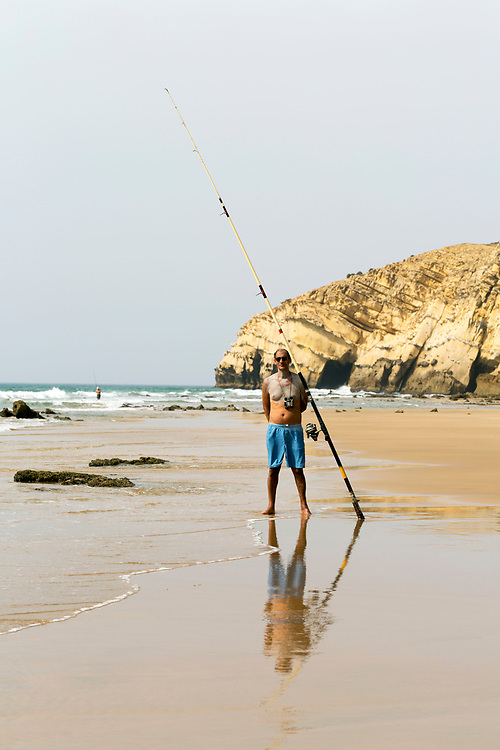 Tourists fishing at the Paradise Beach, Asilah, Morocco, 2015-08-09.<br /><br />Paradise may be somewhat of an over statement, but the beach 2km south of Asilah is worth a visit. <br /><br />Collective taxis run back and forth throughout the day from nearby the Banque Populaire in the centre of Asilah and return back to town from the beach around sunset. <br /><br />Sharing a collective taxi is an interesting adventure in itself, as you pass by unspoilt areas of Morocco's rugged coastline. <br /><br />Known locally as 'Rmilate', the beach is packed full of tourists during the summer months and is best visited off season, when you can expect to have a large space to yourself. <br /><br />Numerous cabin hut restaurants line the base of the cliffs enclosing the beach, serving up freshly grilled sardines, moroccan salads and fish tagines.<br /><br />This beach is much more clean and wild than the main beach strip adjacent to the main town of Asilah. It's worth taking the short collective taxi ride out to this beach when seeking a day out by the seaside rather than camping on the main Asilah beach.