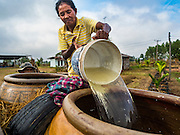 20 JANUARY 2016 - SI LIAM, BURI RAM, THAILAND:  A woman fills water jugs from a pond more than one mile from her home in Si Liam. The drought gripping Thailand was not broken during the rainy season. Because of the Pacific El Nino weather pattern, the rainy season was lighter than usual and many communities in Thailand, especially in northeastern and central Thailand, are still in drought like conditions. Some communities, like Si Liam, in Buri Ram, are running out of water for domestic consumption and residents are traveling miles every day to get water or they buy to from water trucks that occasionally come to the community. The Thai government has told farmers that can't plant a second rice crop (Thai farmers usually get two rice crops a year from their paddies). The government is also considering diverting water from the Mekong and Salaween Rivers, on Thailand's borders to meet domestic needs but Thailand's downstream neighbors object to that because it could leave them short of water.       PHOTO BY JACK KURTZ