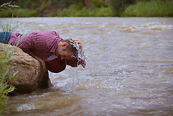 man at a river splashing water on himself while leaning over a rock