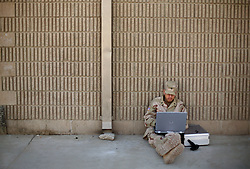 Spec. Christopher Bailey, from the 724th Transportation Company, works on a slide show of his unit's deployment in Iraq, while waiting to go back the United States, Kuwait, Feb. 7, 2005. A member of their unit, Army Spc. Keith Matt Maupin, was taken hostage. He is the only US soldier that is listed MIA from this war.