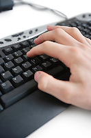 Cropped image of a hand on computer keyboard