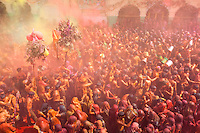 Throngs of sweaty, excited people fling chalk at one another, packed into a plaza to celebrate Holi in India