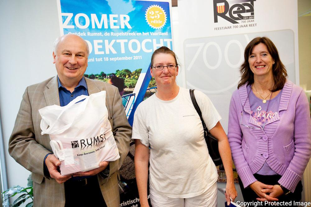 359642-700ste pakket van de Zomerzoektocht gaat de deur uit-Burgemeester Eddy Huyghe, Bianca Cielen (700ste klant) en Anita Verbruggen (toerisme)-Gemeentehuis Reet