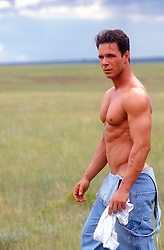 good looking shirtless muscular man walking on a ranch in New Mexico