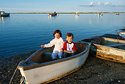 Cute kids pose for a vacation photo in a rowboat.