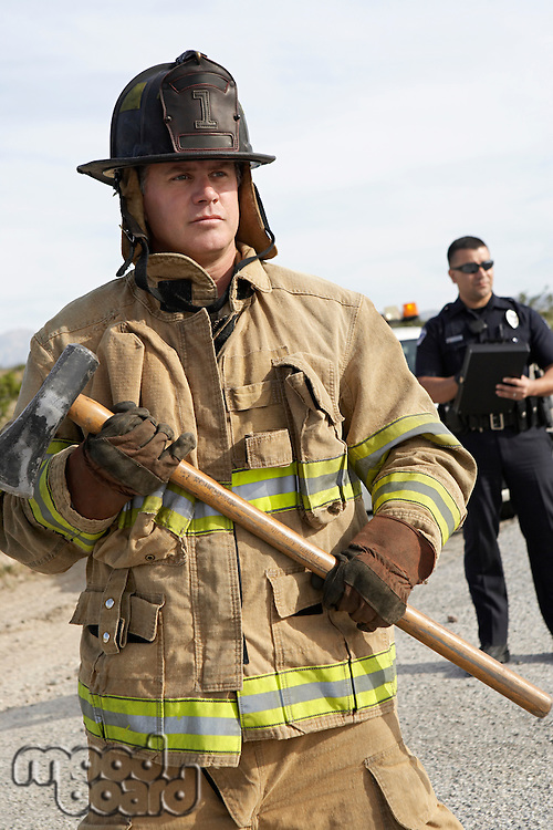 Firefighter with axe, police officer in background