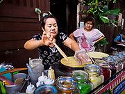16 MAY 2017 - BANGKOK, THAILAND: A street food vendor who makes sweet or savory (dessert or spicy) crepes prepares an order in Pom Mahakan. The final evictions of the remaining families in Pom Mahakan, a slum community in a 19th century fort in Bangkok, have started. City officials are moving the residents out of the fort. NGOs and historic preservation organizations protested the city's action but city officials did not relent and started evicting the remaining families in early March.           PHOTO BY JACK KURTZ
