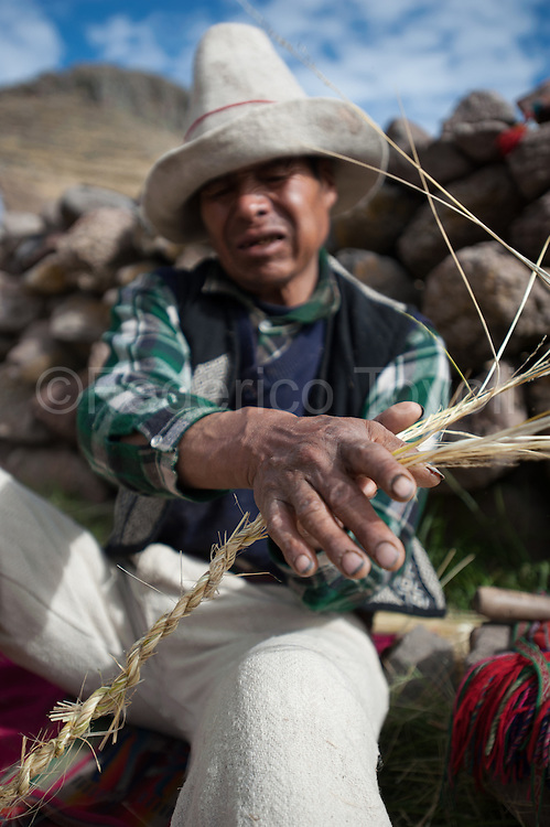 "Andean prist  Cayetano Ccanahuire Puma working the q'oya for to build a rope for the Q'eswachaka bridge. Every member of the four ""comunidades campesinas"" (villages) nearby the bridge have the duty to bring like contribution 40 ""arms"" (60 meters) of rope."