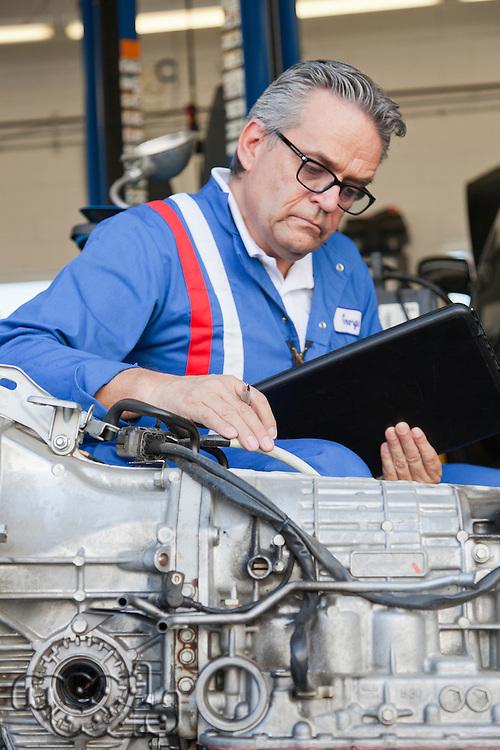 Senior mechanic analyzing car engine and holding clipboard