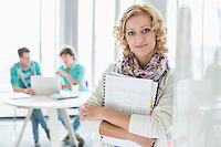 Portrait of creative businesswoman holding files with colleagues working in background at office