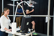 Dr. Lindsay Ludlow (left) and Andrew Udofa (center) work with running legend Ryan Hall at the SMU Locomotor Performance Lab in Dallas, Texas on March 18, 2016. (Cooper Neill for The New York Times)