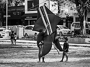 01 AUGUST 2017 - UBUD, BALI, INDONESIA: A man carries his bebean (fish shaped) kite off the public school soccer field in Ubud. Kite flying is a popular past time on Bali. It originally had religious connotations, it was used to ask the gods for bountiful rains and harvests. The kites are large. Small ones, flown by individuals are about two meters long, larger ones flown by teams of up to 80 people are ten meters long. There are three shapes of traditional kites, bebean (fish-shaped), janggan (bird-shaped) and pecukan (leaf-shaped). The pecukan is the most unstable and difficult to fly.    PHOTO BY JACK KURTZ