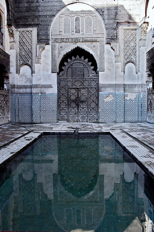 Fes: el Attarine Medersa: reflecting pool in the inner courtyard, looking toward closed carved wooden doors into the lecture hall.