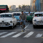 A father and his child ride their bike among traffic of old, vintage cars on the streets of Havana, Cuba