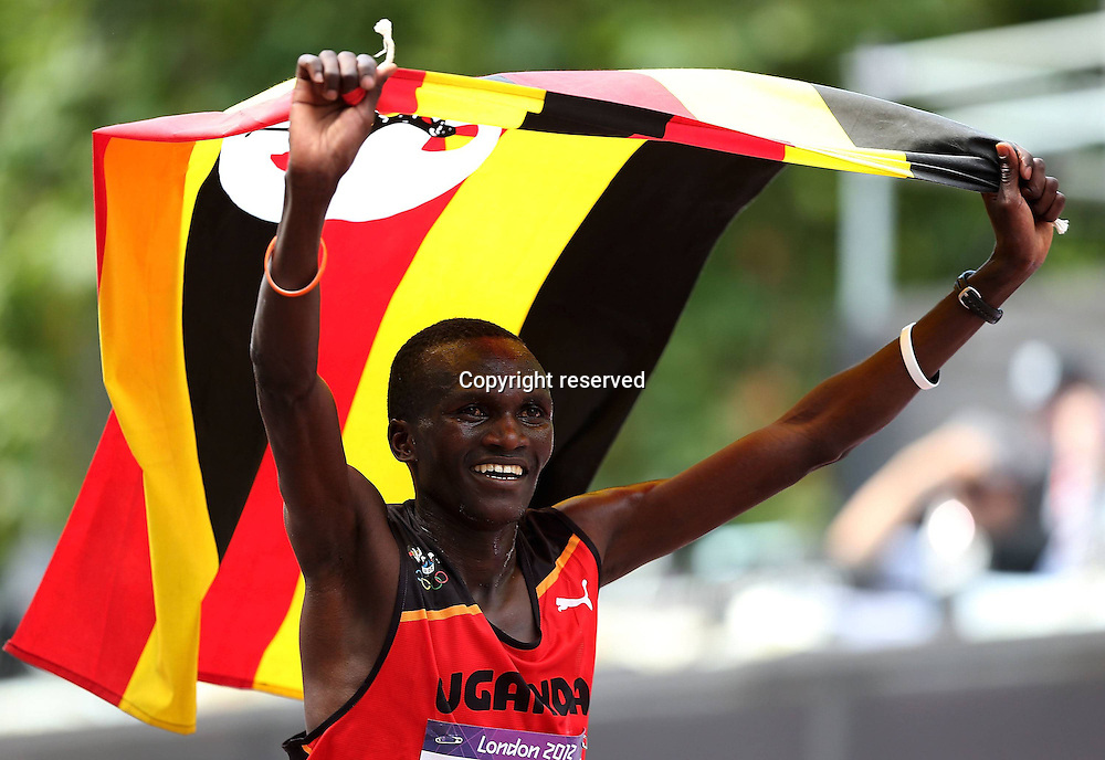 12.08.2012. London, England. Stephen Kiprotich of Uganda finishes as the winner in The Mall and dons his national flag in the mens  Marathon Competition  London 2012 Olympic Games Stephen Kiprotich of Uganda Won Gold Medal