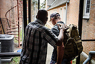 The Rev. Gregory T. Manning, pastor of Gloria Dei Lutheran Church, pats on the back a client of the Broadmoor Food Pantry after assisting him with bagged food next to Gloria Dei on Wednesday, March 9, 2016, in New Orleans. LCMS Communications/Erik M. Lunsford