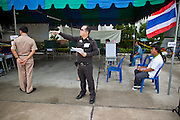 03 JULY 2011 - SAMUT PRAKAN, THAILAND:    A Royal Thai police officer guards a polling place in Samut Prakan, Thailand, Sunday, July 3. More than 47,000,000 Thais were registered to vote in Sunday's election, which had turned into a referendum on the current government, led, by the Thai Democrats and the oppositionPheu Thai party. Pheu Thai is the latest political incarnation of ousted Thai Prime Minister Thaksin Shinawatra. PT is led by his youngest sister, Yingluck Shinawatra, who is the party's candidate for Prime Minister. Exit polling by three Thai polling firms showed Pheu Thai winning a landslide election.    PHOTO BY JACK KURTZ