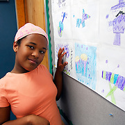 Jazmine her personality expresses itself through her drawings and helps her to open up to others. This is a characteristic of her autism she is in an Exceptional Education Class. Standing in front of an exhibition of her art work in the classroom.