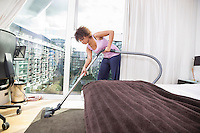 African American woman vacuuming in bedroom
