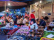 11 SEPTEMBER 2013 - BANGKOK, THAILAND:  People eat at Lek and Rut Seafood stand in the Chinatown section of Bangkok. Lek and Rut Seafood was one of the first street stall restaurants in Bangkok and is more of a pop up restaurant than a street food stall. It has sit down service and full menus, but seating is on the street and sidewalk and food is prepared in portable cookers that are brought out to the street when the restaurant opens. Thailand in general, and Bangkok in particular, has a vibrant tradition of street food and eating on the run. In recent years, Bangkok's street food has become something of an international landmark and is being written about in glossy travel magazines and in the pages of the New York Times.        PHOTO BY JACK KURTZ