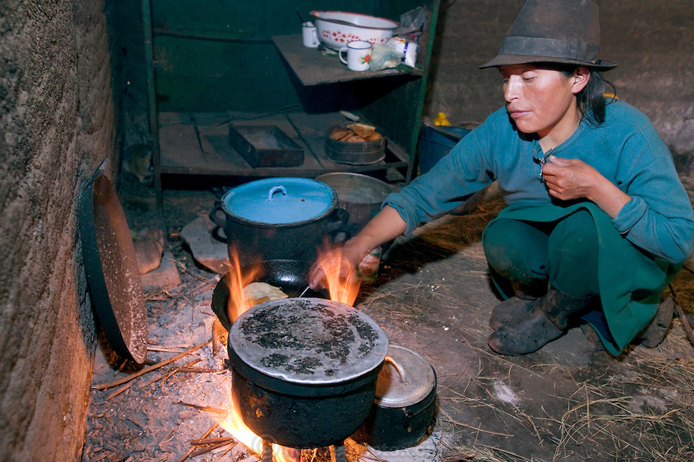 Maria Ermelinda Ayme Sichigalo, a farmer and mother of eight prepares dinner for her family in her adobe kitchen house in Tingo village, central Andes, Ecuador. (From the book What I Eat: Around the World in 80 Diets.) The caloric value of her typical day's worth of food in the month of September was 3800 kcals. She is 37 years of age; 5 feet, 3 inches tall and 119 pounds. With no tables or chairs, Ermelinda cooks all the family's meals while kneeling over the hearth on the earthen floor, tending an open fire of sticks and straw. Guinea pigs that skitter about looking for scraps or spilled grain will eventually end up on the fire themselves when the family eats them for a holiday treat. Because there is no chimney, the beams and thatch roof are blackened by smoke. Unvented smoke from cooking fires accounts for a high level of respiratory disease and, in one study in rural Ecuador, was accountable for half of infant mortality.  MODEL RELEASED.