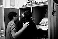 Mekarius (L) comforts his mother (Sanaa) in Medo's bedroom. Nag Hamadi, Egypt.
