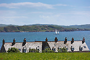 Sailboat passing rooftops of homes on Isle of Iona in the Inner Hebrides and Western Isles, West Coast of Scotland