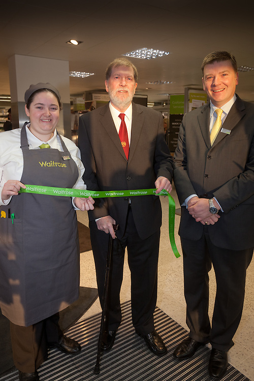 St Savior Constable ( mayor) Peter Hanning  cuts the ribon held by Catriona Dunleavy ( it is her 30th birthday on the opening day and the Store manager Duncan Langstone