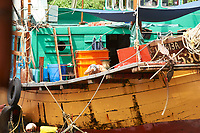 Crew member washing his hair on Fishing boat moored in Aberdeen fishing village