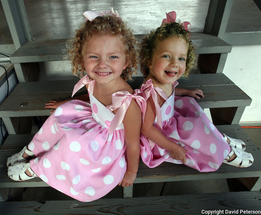 "Even though they are dressed alike, and have curly blond hair,  3-year-old twins Devon, left, and Darrah, from Pleasantville, Iowa, were entered in the ""least look alike"" category of the Twins, Triplets and More Contest at the Iowa State Fair in Des Moines, Iowa in 2007."