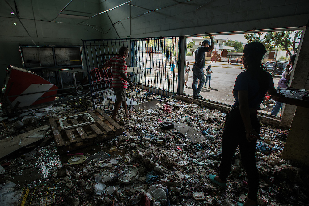 CUMANÁ, VENEZUELA - JUNE 16, 2016:  People search for anyting they can salvage from a grocery store that was destroyed last Tuesday by hundreds of looters in Cumaná, Venezuela. They made it through the doors before the owners could close them, forced a large metal gate open so those outside could pour inside. They took water, flour, corn meal, salt, sugar, potatoes, cereal—leaving behind only a broken freezers and overturned shelves. And they proved that even in country with the richest oil reserves in the world, it was possible for people to riot because there was no food. Venezuela is convulsing from a raft of violence triggered by hunger. It is latest chapter of an economic collapse which has left the country neither able to produce its food nor import it from abroad, leaving a nation searching for how to feed itself. In the past 11 days, scores of businesses, mostly stores, have been looted or destroyed and five people have died in the confrontations. With delivery trucks under constant attack, the nation's food is now transported under armed guard. Entire cities have been militarized under an emergency decree from President Nicolás Maduro; bakeries are now watched over by the National Guard.  PHOTO: Meridith Kohut for The New York Times