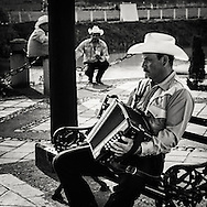 Accordion player from a Mexican street Mariachi band sitting on a bench waiting for the next gig