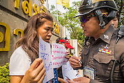 25 JANUARY 2013 - BANGKOK, THAILAND: A Thai police officer interviews a free speech demonstrator in front of the Criminal Court building in Bangkok. About 70 people protested on behalf of freedom of speech and expression at the Criminal Court building in Bangkok Friday. The protest was called as a result of the 10 year sentence handed down against magazine editor Somyot Prueksakasemsuk on Lese Majeste charges earlier in the week. The protesters burned several legal documents to demonstrate they said was their loss of free speech during the protest.     PHOTO BY JACK KURTZ