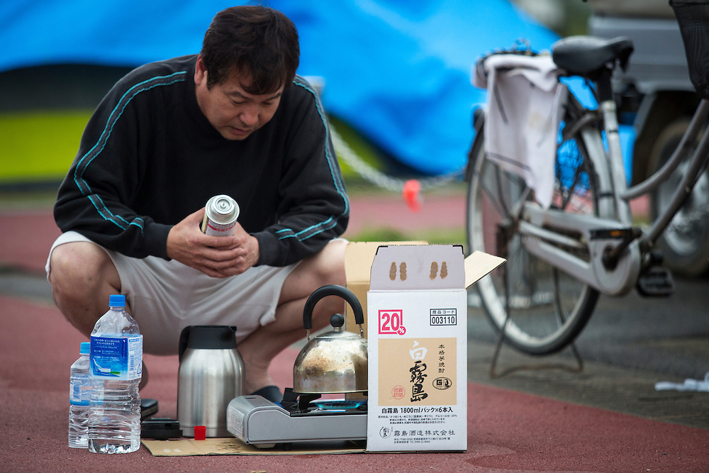 KUMAMOTO, JAPAN - APRIL 21: A man boing hot water in early early morning on April 21, 2016 in Mashiki Gymnasium parking area, Kumamoto, Japan. Over hundreds of evacuees sleep in the car and survivors face health threat, health experts says, 20 people diagnosed in Mashiki, one has died and 2 are in critical condition.<br /> As of April 45 people were confirmed dead after strong earthquakes rocked Kyushu Island of Japan. Nearly 11,000 people are reportedly evacuated after the tremors Thursday night at magnitude 6.5 and early Saturday morning at 7.3.<br /> <br /> Photo: Richard Atrero de Guzman