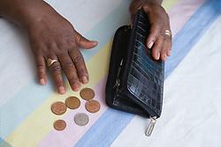 Elderly woman counting money from her purse,