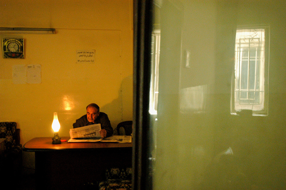 An official reads a newspaper by lamp light in a court justice building. One year after the war to topple the regime of Saddam Hussein, power cuts are still common place.<br /> Baghdad, Iraq. 24/04/2004