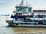 20 NOVEMBER 2017 - YANGON, MYANMAR: The Dala Ferry crosses the Yangon River. Tens of thousands of commuters ride the ferry every day. It brings workers into Yangon from Dala, a working class community across the river from Yangon. A bridge is being built across the river, downstream from the ferry to make it easier for commuters to get into the city.     PHOTO BY JACK KURTZ