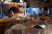 Vendors display bushels of beans for sale at a market in Sanaa, Yemen as a merchant walks by with a glass of tea.