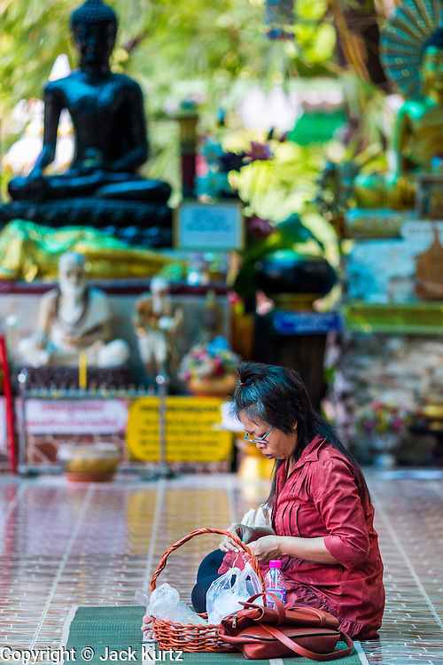 15 JULY 2014 - BANGKOK, THAILAND:    A woman prays in a shrine at Wat Rachathiwat Ratchaworawihan on Samsen Soi 9. The temple has a large teak instruction hall, considered one of the finest teak buildings in Asia.   PHOTO BY JACK KURTZ