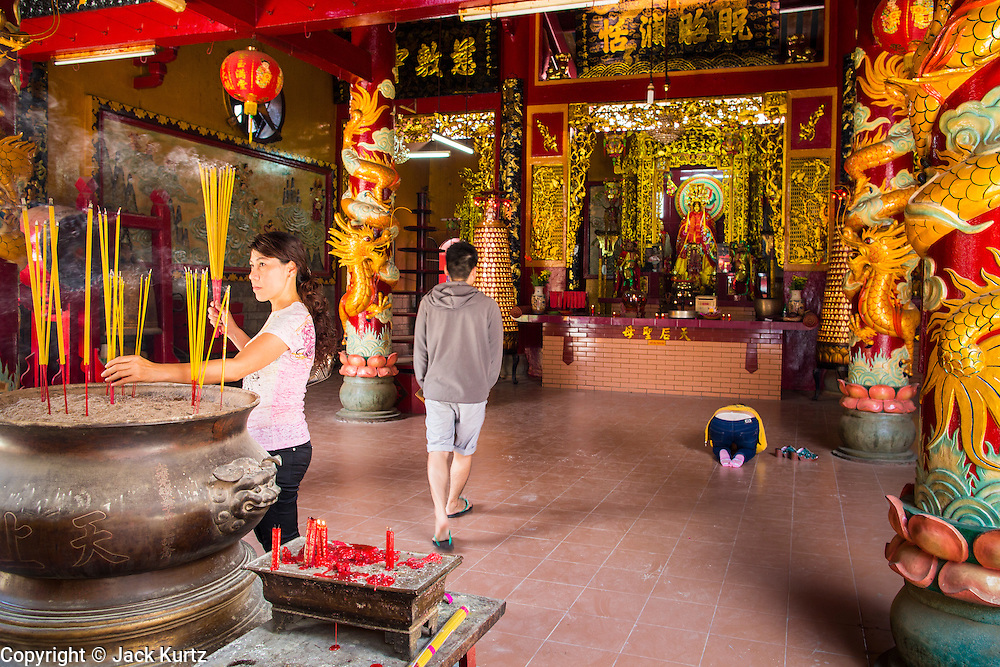 "12 APRIL 2012 - HO CHI MINH CITY, VIETNAM:  People pray in the entry way of Chùa Quan Âm (Avalokiteshvara Pagoda), a Chinese style Buddhist pagoda in Cho Lon. Founded in the 19th century, it is dedicated to the bodhisattva Quan Âm. The pagoda is very popular among both Vietnamese and Chinese Buddhists. Cholon is the Chinese-influenced section of Ho Chi Minh City (former Saigon). It is the largest ""Chinatown"" in Vietnam. Cholon consists of the western half of District 5 as well as several adjoining neighborhoods in District 6. The Vietnamese name Cholon literally means ""big"" (lon) ""market"" (cho). Incorporated in 1879 as a city 11 km from central Saigon. By the 1930s, it had expanded to the city limit of Saigon. On April 27, 1931, French colonial authorities merged the two cities to form Saigon-Cholon. In 1956, ""Cholon"" was dropped from the name and the city became known as Saigon. During the Vietnam War (called the American War by the Vietnamese), soldiers and deserters from the United States Army maintained a thriving black market in Cholon, trading in various American and especially U.S Army-issue items.       PHOTO BY JACK KURTZ"