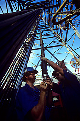 Stock photo of an upward view of two men working on oil pipes