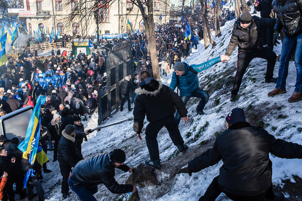 KIEV, UKRAINE - DECEMBER 14: People help others climb up a snowy hill at a pro-government rally on December 14, 2013 in Kiev, Ukraine. Thousands of people have been protesting against the government since a decision by Ukrainian president Viktor Yanukovych to suspend a trade and partnership agreement with the European Union in favor of incentives from Russia. (Photo by Brendan Hoffman/Getty Images) *** Local Caption ***