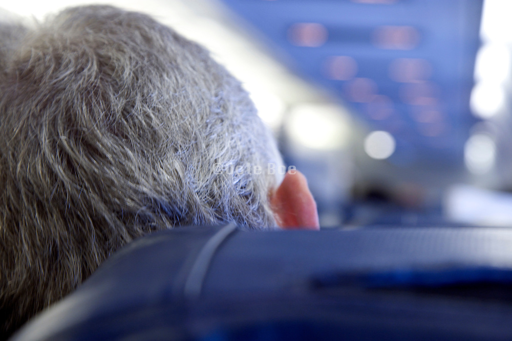 graying businessman sitting in an airplane