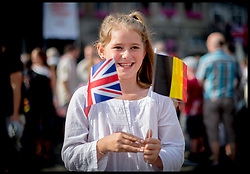 licensed to i-Images Picture Agency. 04/08/2014. Mons, Belgium. People wait in the Square with flags to see The Duke and Duchess of Cambridge and Prince Harry arrive for  a Reception at Mons Town Hall in Belguim as part of series of events to commemorate  the 100th anniversary of the start of the First World War. Picture by Andrew Parsons / i-Images
