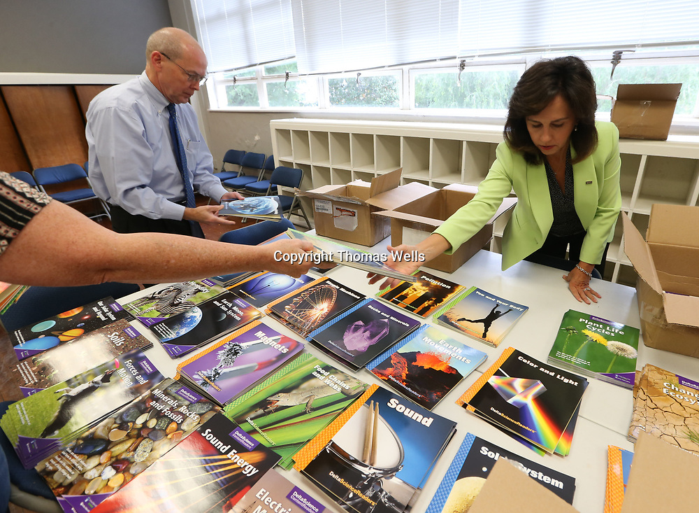 Rotary Club volunteers Jerry Jones, left, Zelda Dexter seperate all the STEM curriculum books the club bought for the Tupelo Public School District.