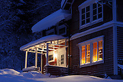 Inviting lights shine from the porch and the lighted transom windows of this traditional Swedish farm house in winter.