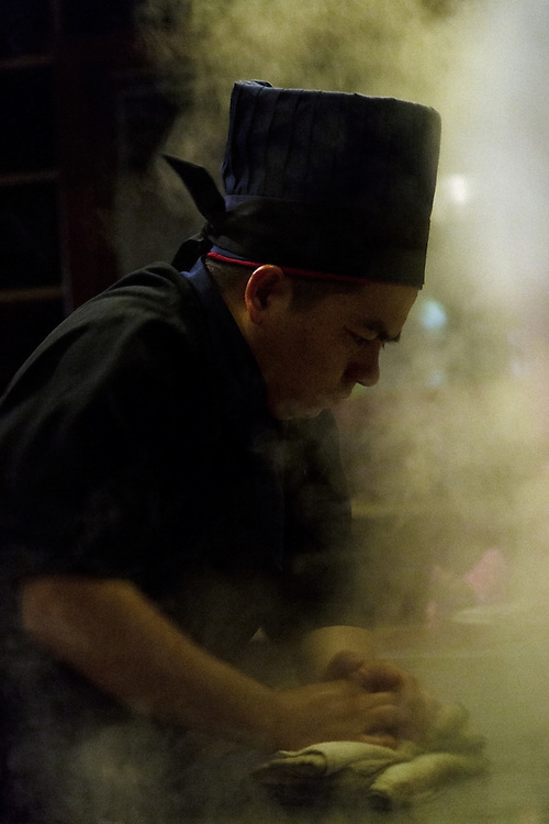 A Hibachi Chef, enveloped in steam cleans his cooking surface after preparing a meal.